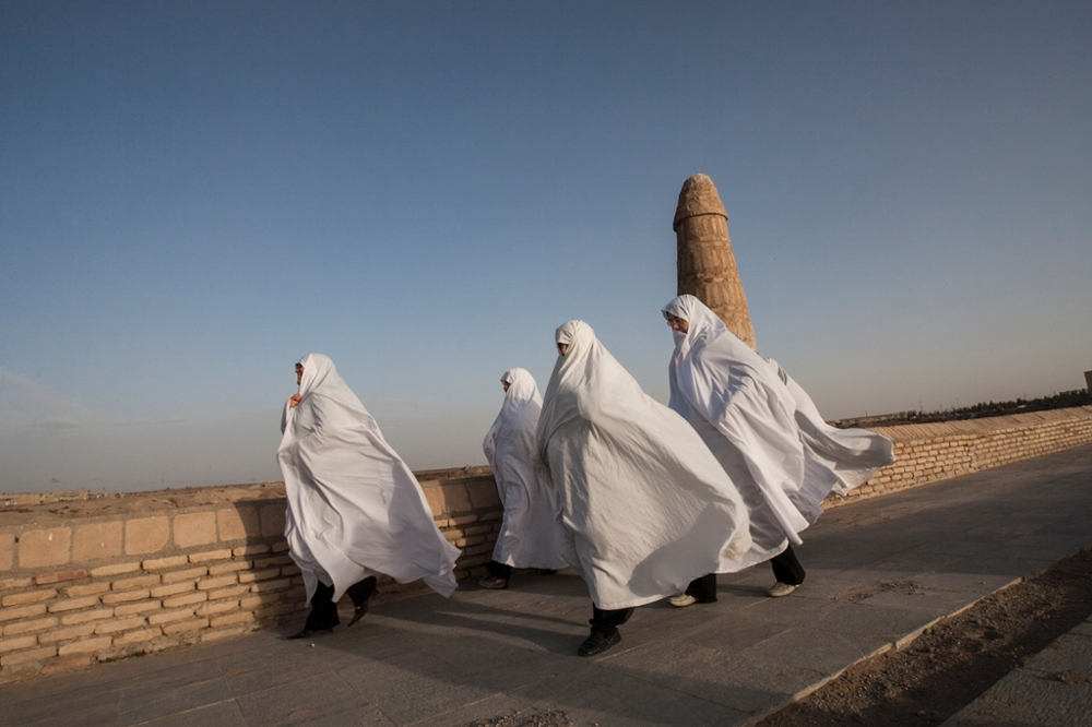 Iran, Varzaneh, Isfahan Province, A group of women, dressed in white chadors, crossing the Varzaneh bridge. Traditionally, in the region, white is worn to ward off evil.