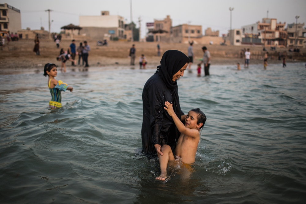 Iran, bushehr, A woman wading in Persian gulf with her son.