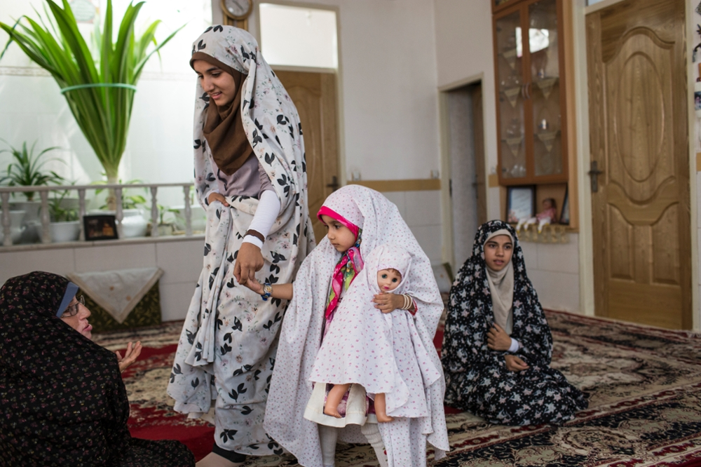 Iran, Yazd, The female members of a family at their home where even the youngest girl wears a chador.