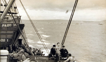 Troops on Board a Landing Craft at D Minus 1 Sit Around on Deck, Mostly Silent, and Look at the Last Glimpses of the Mainland Behind Them