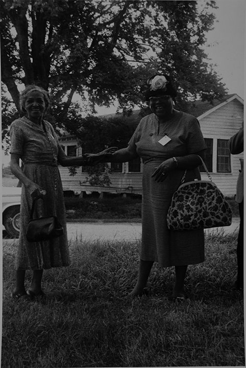 Mt. Bayou, MS. Two elderly women holding hands.