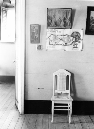 White Chair & Malaria Poster in Guesthouse, Manati