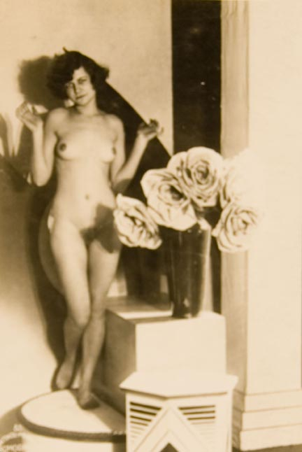 Untitled #85 (nude woman on pedestal, vase with large flowers)