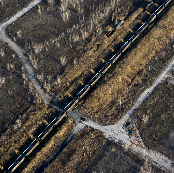 Petcoke filled train moving through brown field, former steel mill site