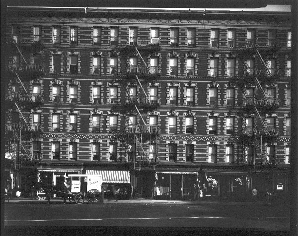 Untitled (front view of building with storefronts and horse drawn cart)