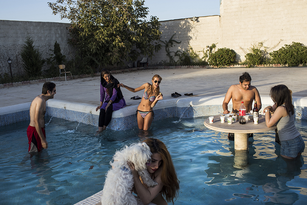 Tehran, Iran. A group of young people relax and drink in a swimming pool in Tehran.