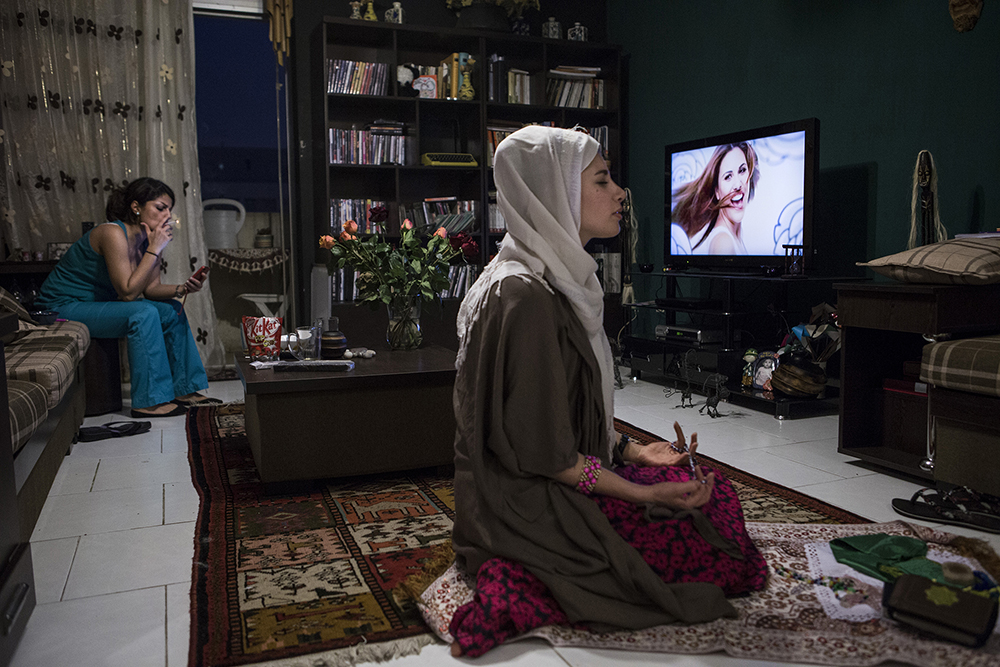 Tehran, Iran. A woman prays while her friend is smoking and watching television.