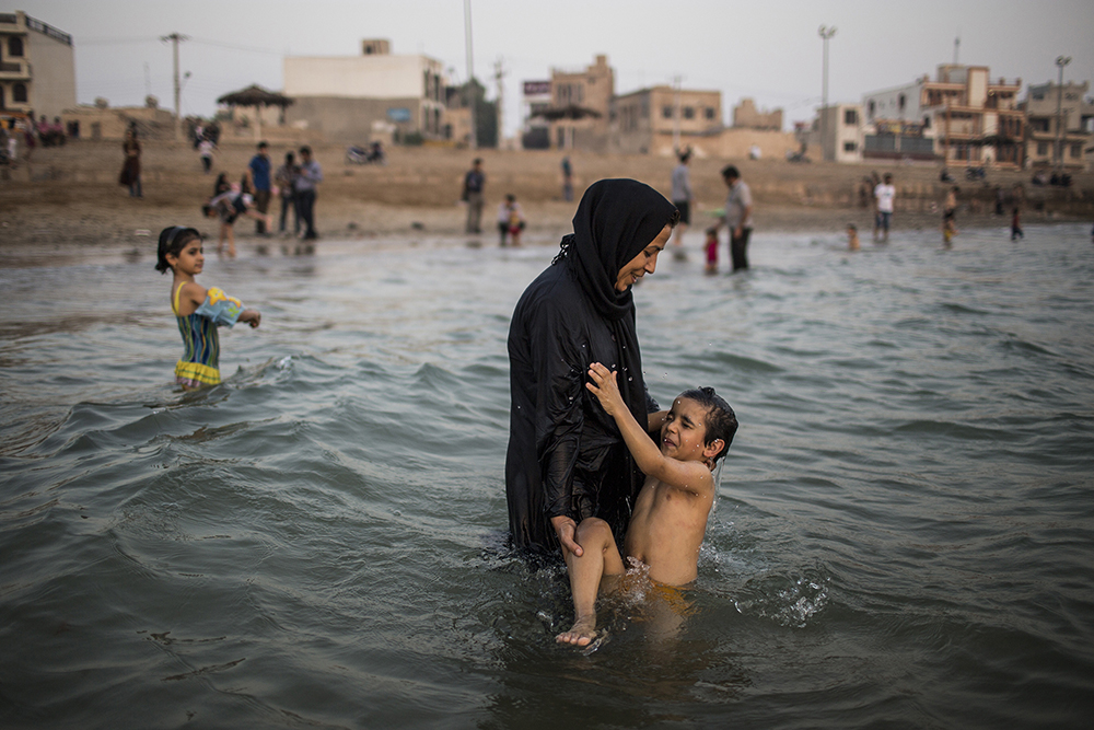 Bushehr, Iran. A woman wading in the Persian gulf with her son.