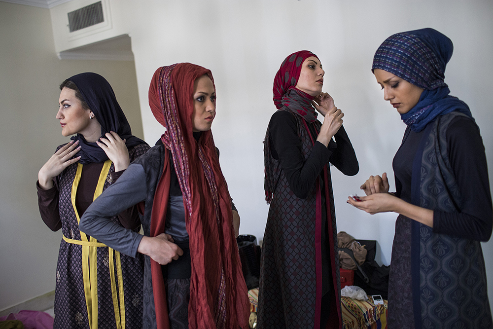 Tehran, Iran. A group of models apply makeup before a photo shoot.