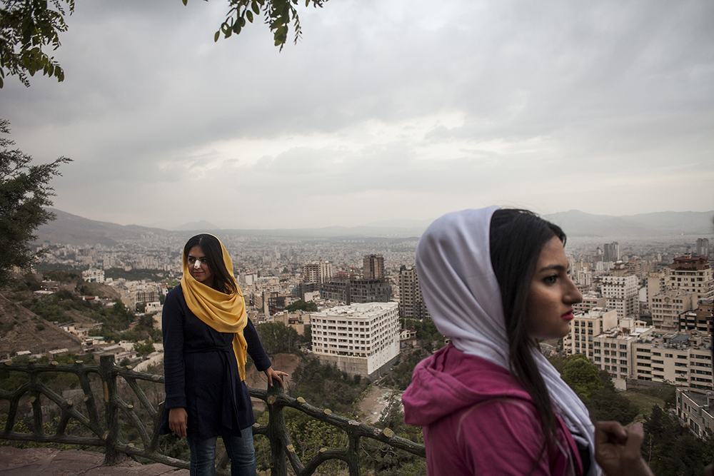 Tehran, Iran. A group of young women stand on a terrace at Bam-e Tehran, the 'roof of Tehran,' an area overlooking the capital. One of the young women has a dressing on her nose following plastic surgery. Iran has the highest rate of nose surgery in the world with a reported 200,000 operations taking place each year.