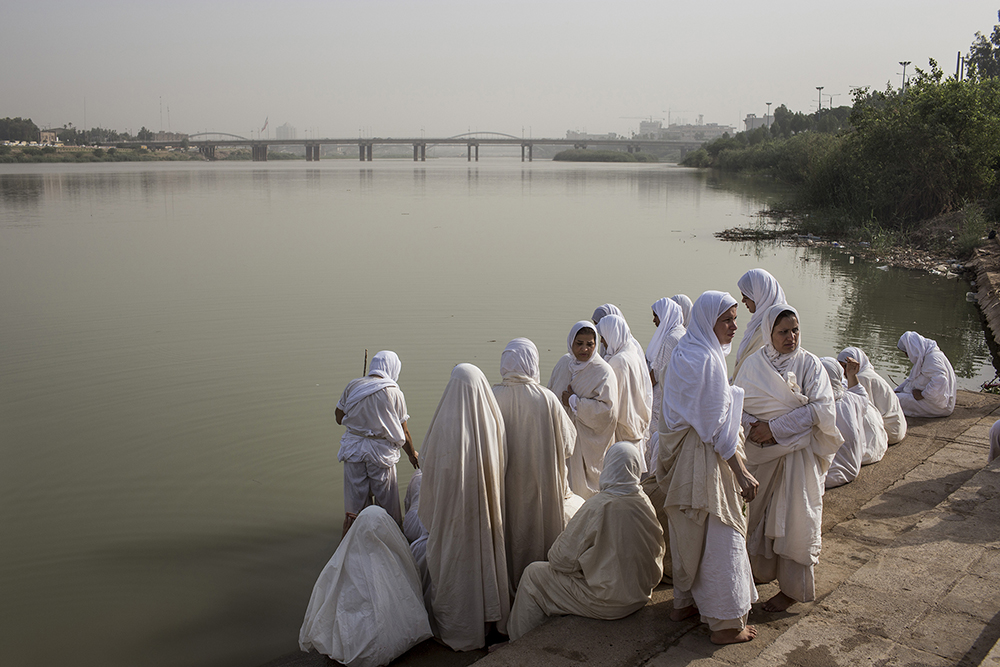 Ahvaz, Iran. Female members of the ancient Sabaean Mandean religious sect perform a ritual cleansing during an annual baptism held on the banks of the Karoun River. Water is everything to the Sabaean Mandeans who are baptized in it, get married in it, and receive their last rites by the river's edge.