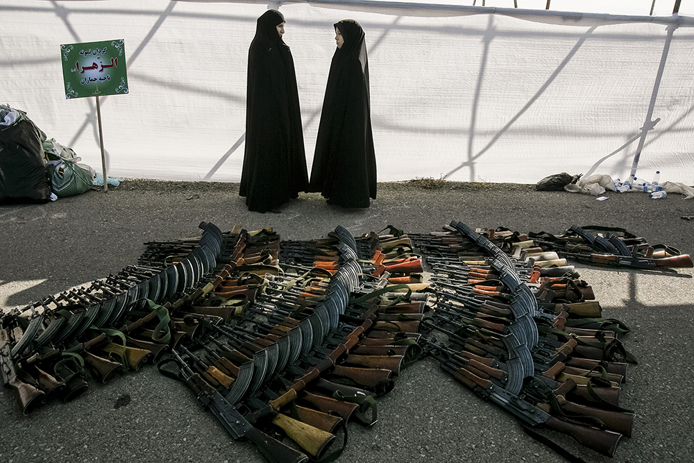 Tehran, Iran. Female members of the Basij, a voluntary militia, stand next to a pile of AK-47s following a military parade held to mark Basij Week.