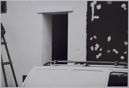 Untitled (top of vehicle next to black/white wall)