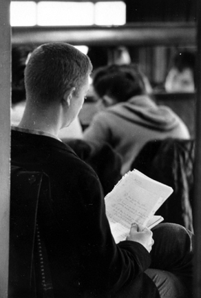 Untitled (young man reading notes in school)