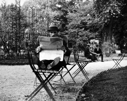 Jardin de Luxembourg (man reading newspaper with feet on chair)