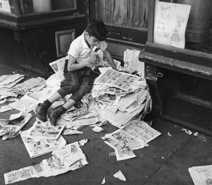 New York (boy eating ice cream on pile of newspapers)