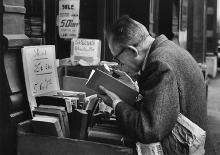 Fourth Avenue, New York (man with loop reading at book stand)