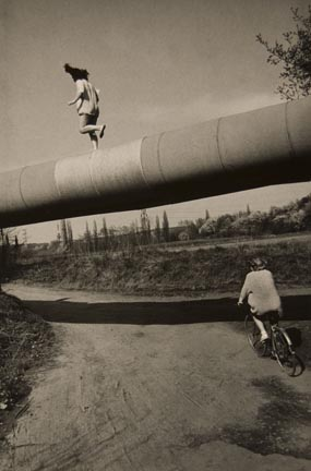 Untitled (Two youths: one walking on pipeline, one riding bike), from the
