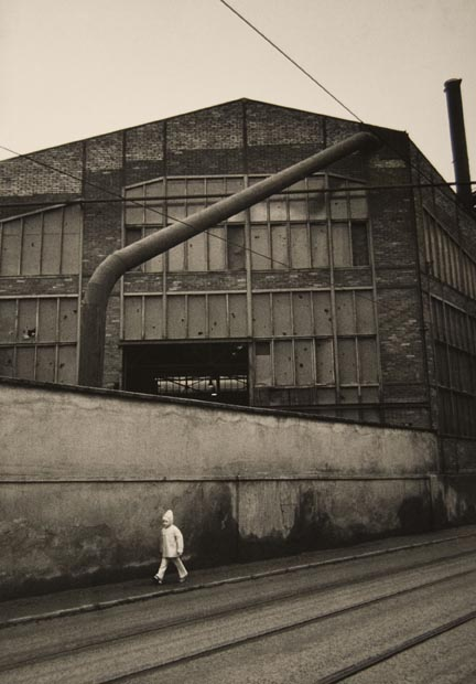 Untitled (child walking by factory wall), from the
