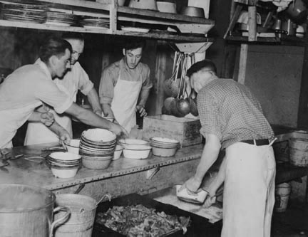 Dishing out and serving food in logging camp near Effie, Minnesota
