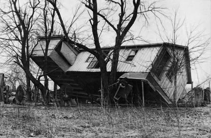 Upturned farmhouse resting against a tree. Result of the flood in Posey County, Indiana