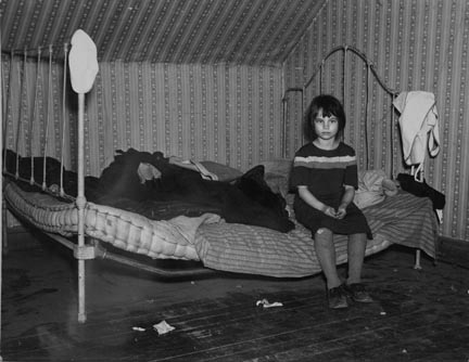 One of Edgar Allen's children sitting on the bed in the house on his farm. There are no sheets, pillowcases, or pillows (other than makeshift) in use. Bedding usually consists of castoff rags and a few old blankets. Near Milford, Iowa. They are helped by the Resettlement Administration
