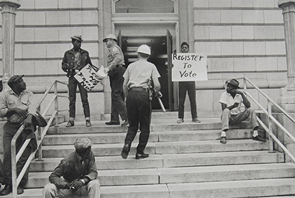 Sheriff Jim Clark arrests two demonstrators who displayed placards on the steps in front of the federal building in Selma
