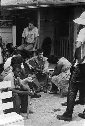 After giving a concert in a cotton field in Greenwood, Bob Dylan plays behind the SNCC office. Bernice Reagon, one of the original Freedom Singers and today leader of Sweet Honey in the Rock, listens. Mendy Sampstein sits behind Dylan and talks to Willie Blue
