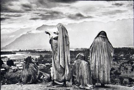 Srinagar, Kashmir, Muslim women on the slopes of Hari Parbal Hill, praying toward the sun rising behind the Himalayas, from the