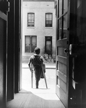 Washington, D.C. Young boy standing in the doorway of his home on Seaton Road in the northwest section. His leg was cut off by a streetcar while he was playing in the street