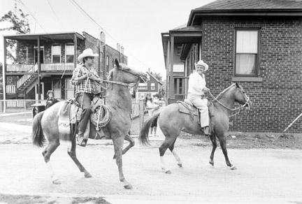 Two Men on Horses Go To Start of the Mexican Parade at the School Yard, September 1987