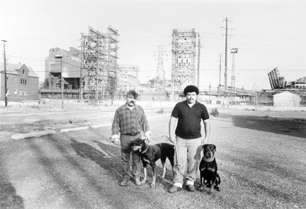 Two Men and Their Dogs on an Abandoned Steel Mill Parking Lot