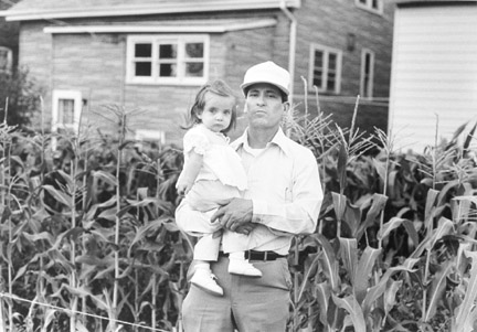 A Man and Child Near a Corn Shack Growing in a Neighbor's Backyard, July 1988