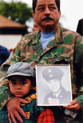 A Child and His Uncle Attend the Annual Southeast Side Vietnam Veterans Memorial While Holding a Photo of a Family Member, Joseph Quiroz, Outside of Our Lady of Guadalupe Parish. Quiroz Died While Serving his Country in Vietnam, September 2000