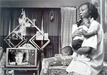 Woman holding young girl while boy watches white woman on TV, Cabrini-Green, from Changing Chicago