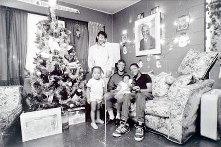 Family on sofa with xmas tree and presents, photo of Harold Washington on wall, Cabrini-Green, from Changing Chicago
