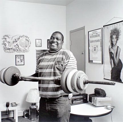 Young man lifting weights in his room at the Harold Washington SRO, from the Edge of Shelter Project