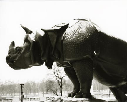 A statue of a rhinoceros.  Trees and telephone wires are in the background.