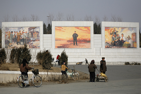 Koreans walk past massive propaganda mosaics of Kim Jong Il and Kim Il Sung on the outskirts of Pyongyang, North Korea